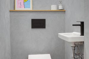 Toaleta s betonovou stírkou a kresleným aktem