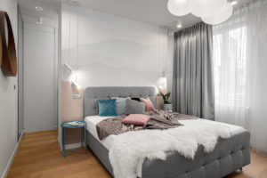 Šedá ložnice s barevnými polštářy a dubovou podlahou