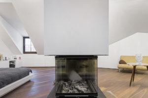 Dominantní krb v podkrovním obývacím pokoji