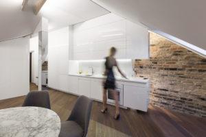 Bílá lesklá kuchyň v podkroví a žena