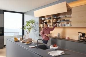 Žena v moderní kuchyni otevírá vrchní police
